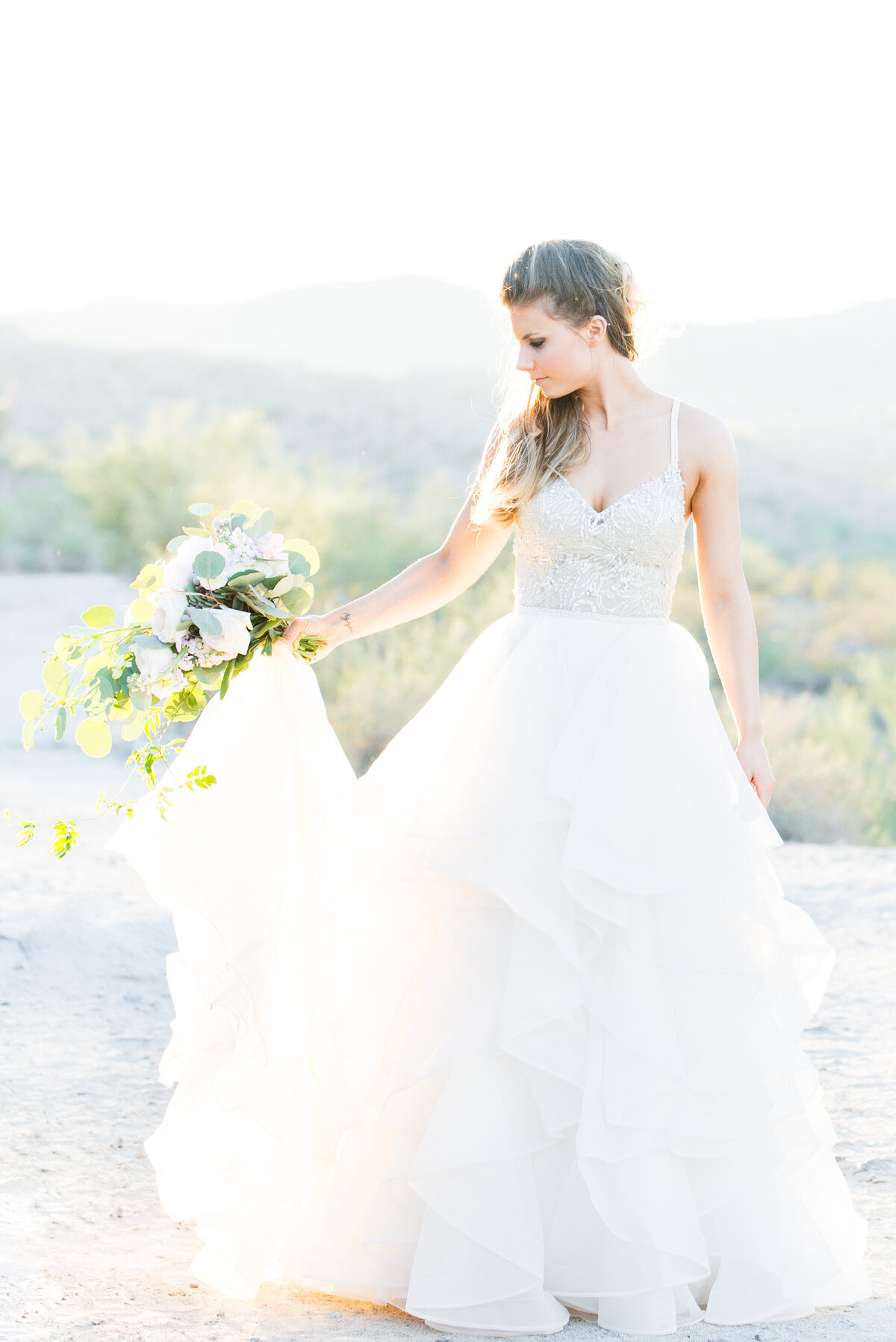 A bride swishes her Watters dress while being photographed in the Arizona desert
