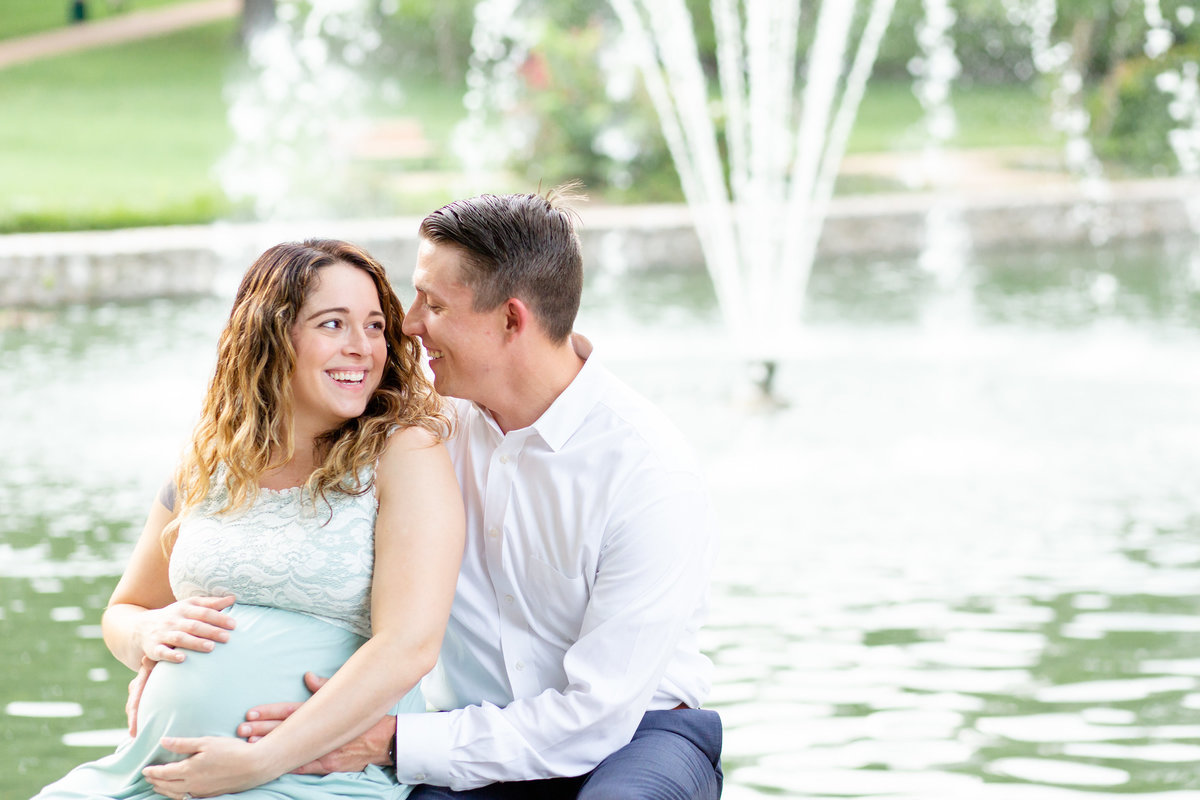 Summer Sunset Maternity Session with maxi dress sitting by fountain  at Oak Knoll Park in St. Louis by Amy Britton Photography Photographer  in St. Louis