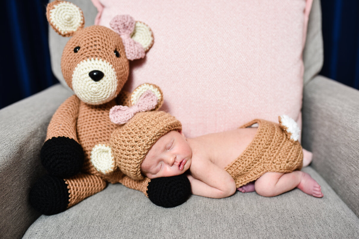 Beautiful lifestyle newborn photography: Baby girl with handmade deer and matching outfit in her nursery in Mississippi