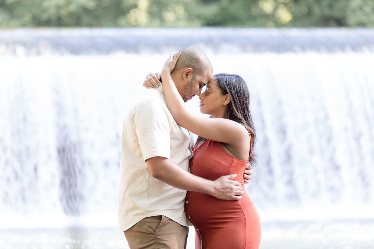 pregnant wife and husband embrace in front of waterfall