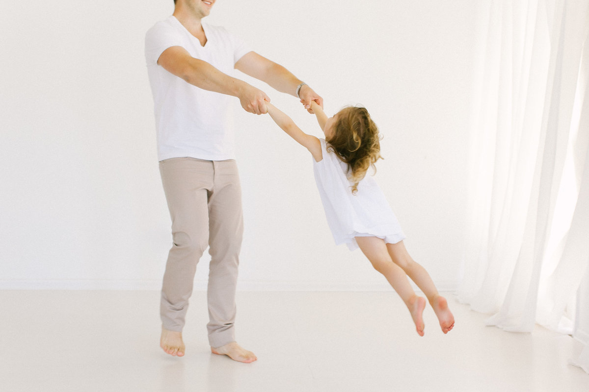 Father dancing and twirling his daughter in Laurie Baker's white studio