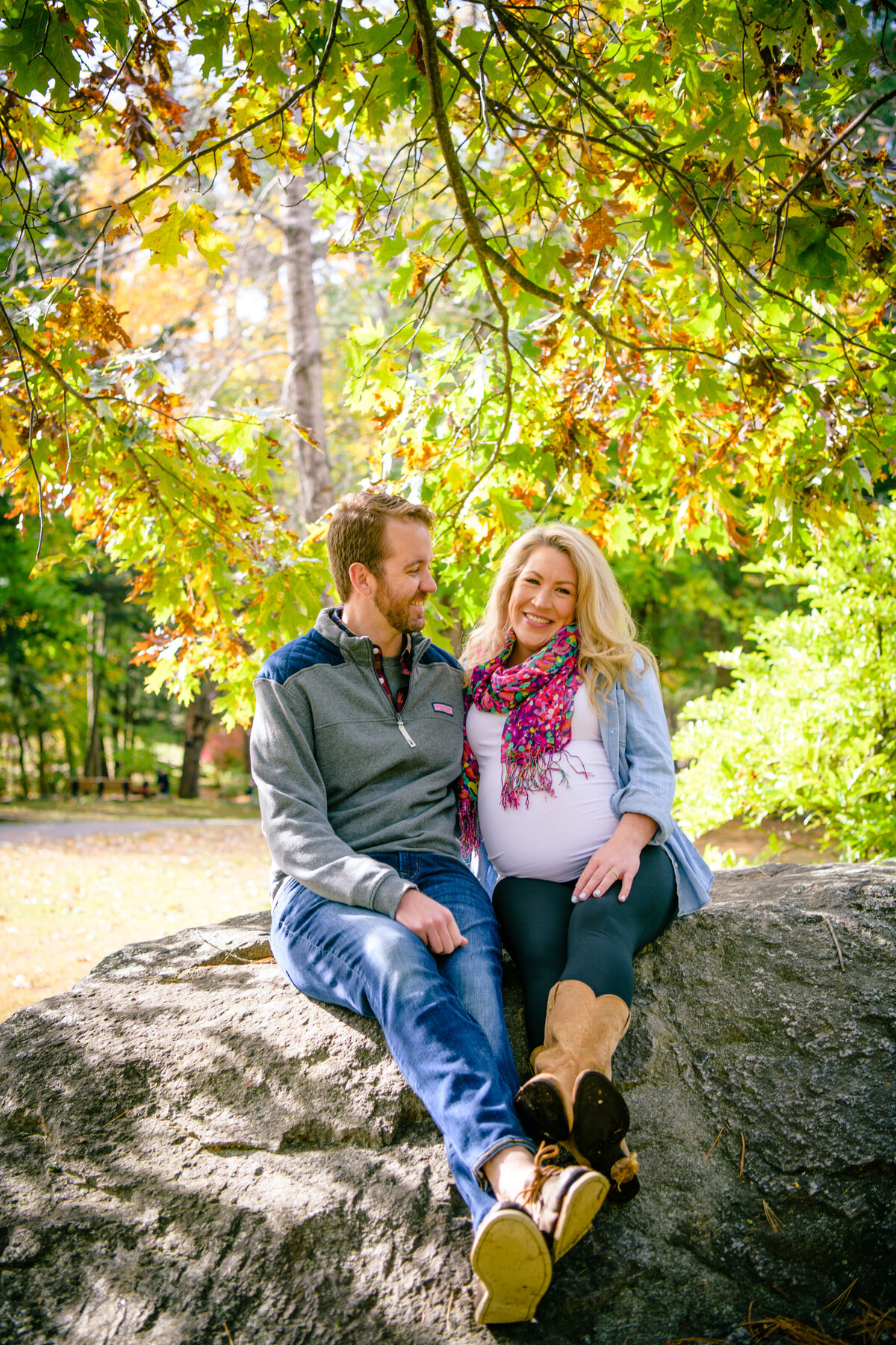 Benson Park maternity session with couple sitting on rock