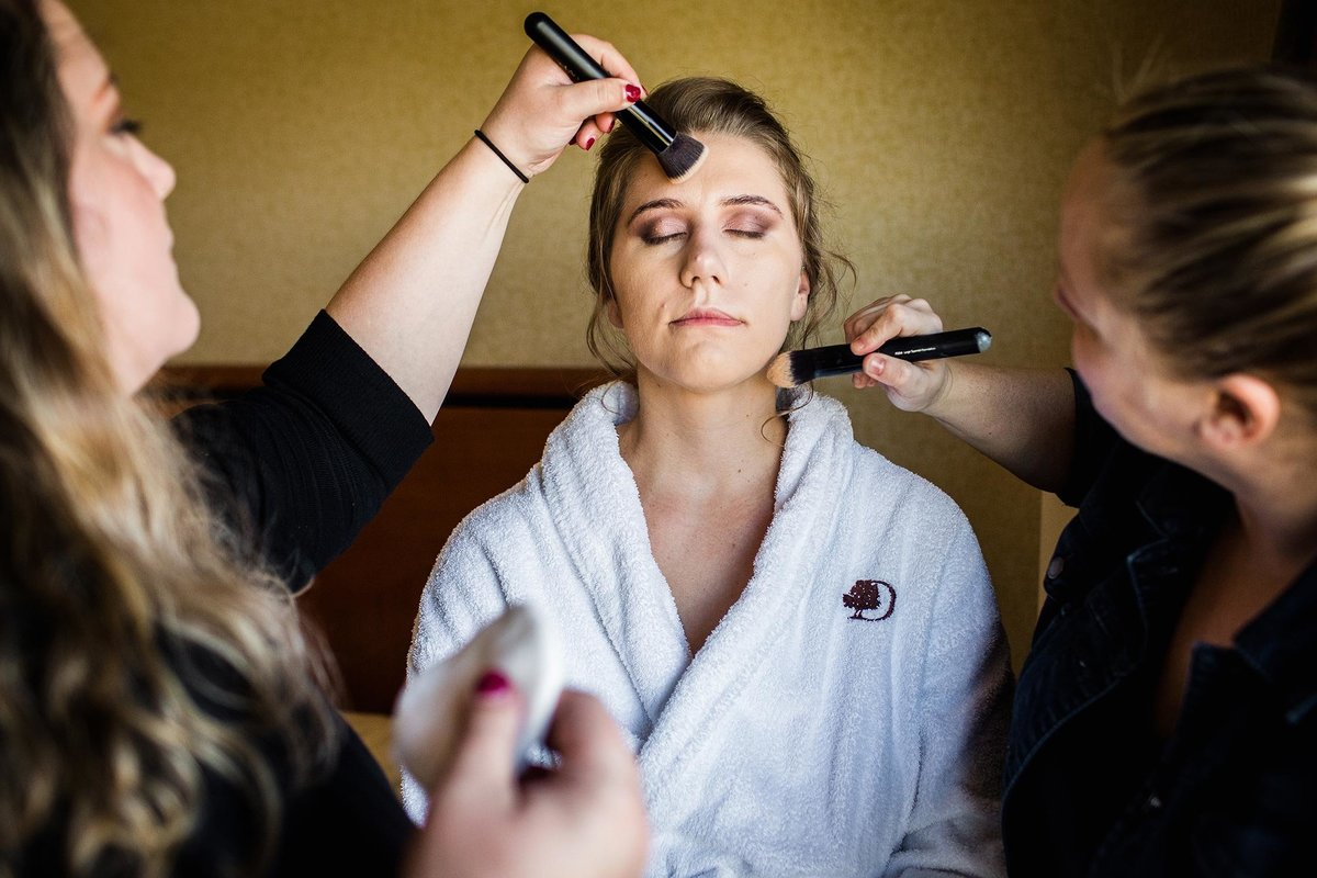 A bride has her makeup done before her Alter Brewery wedding.