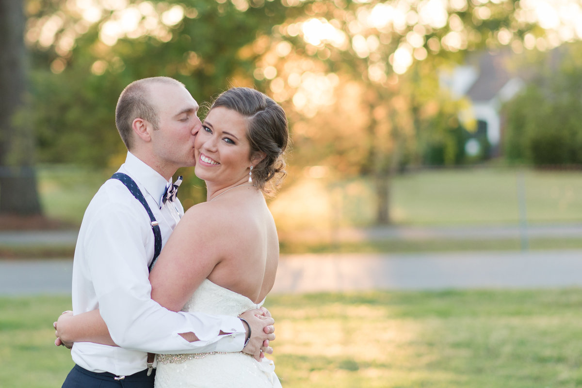 Groom kissing bride under warm sunset light at Planter's Club