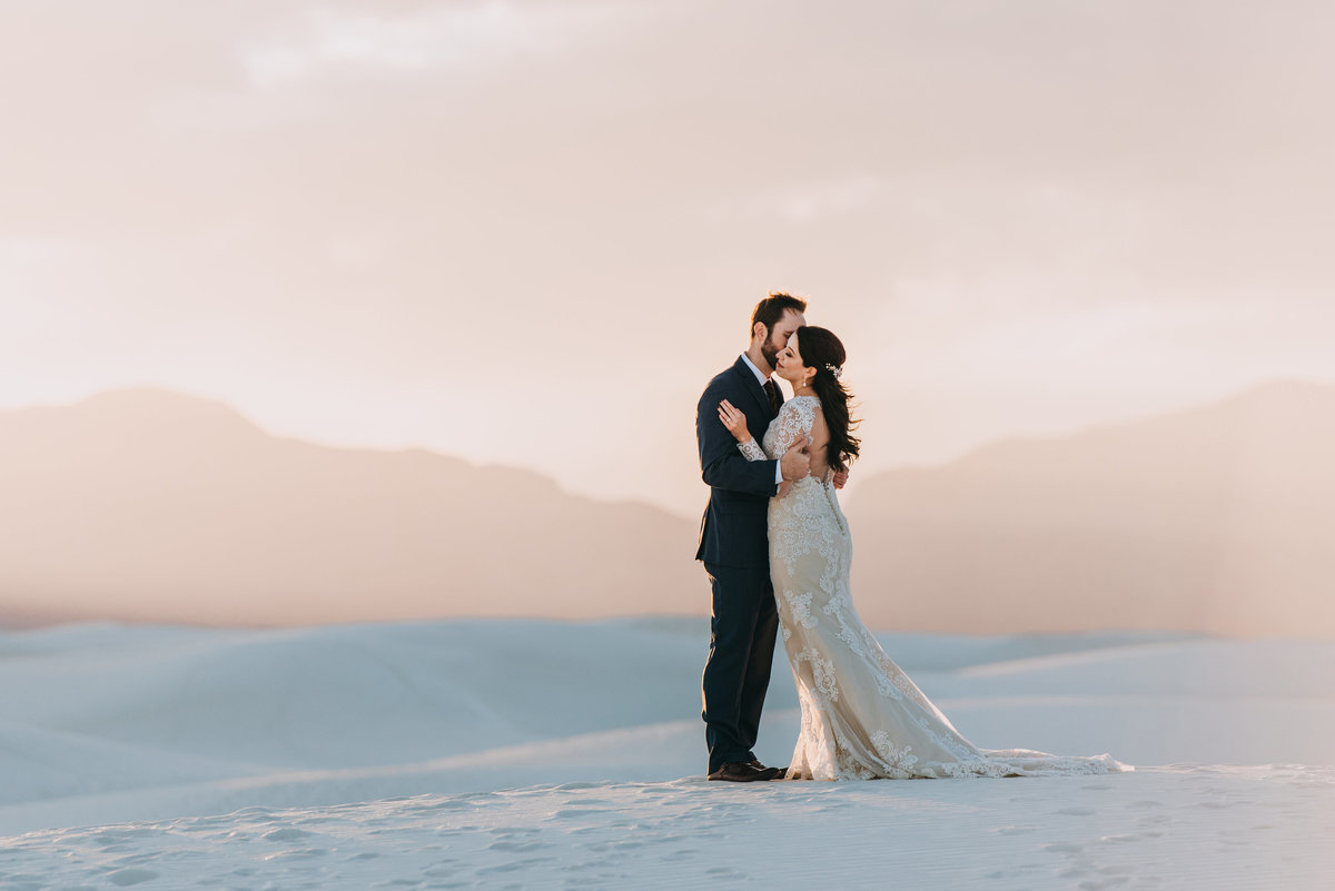Couple embraces with emotion as sun sets at White Sands New Mexico