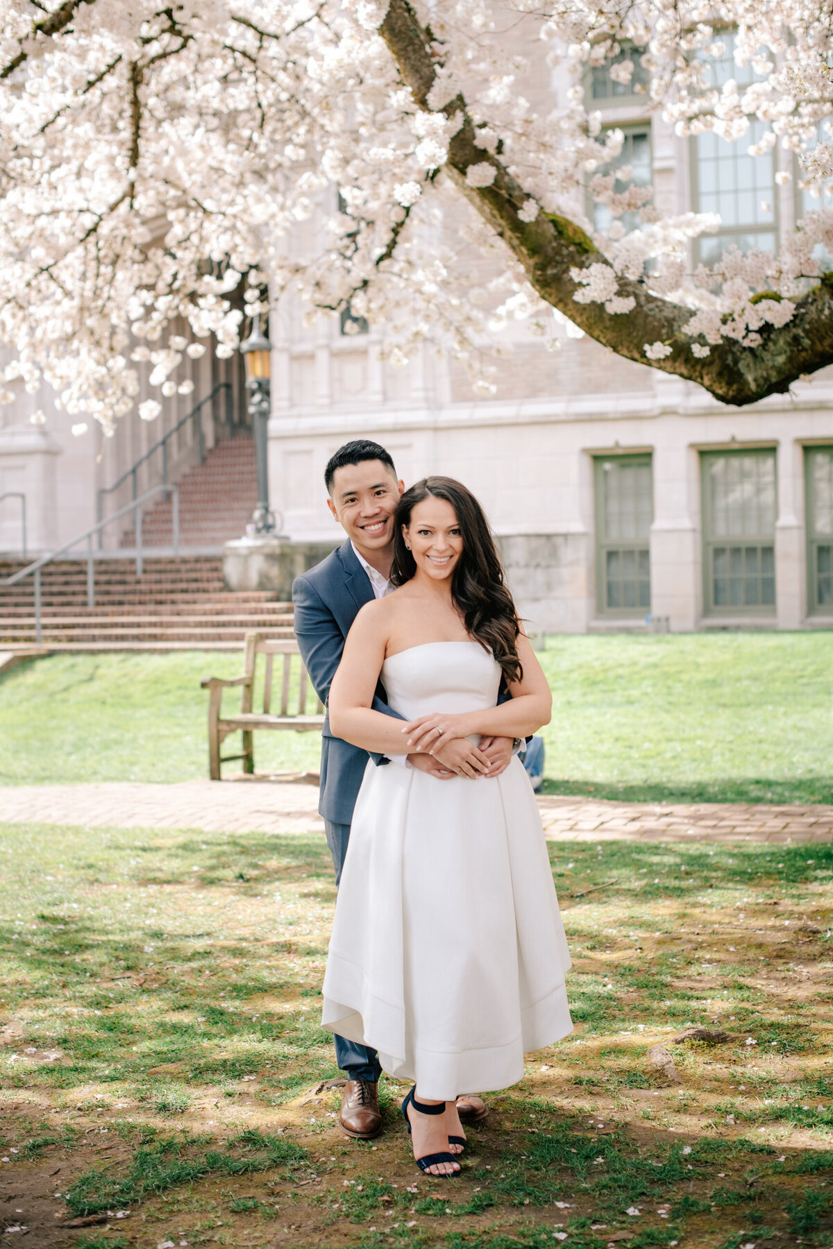 Couple standing by cherry blossoms at University of Washington in Seattle