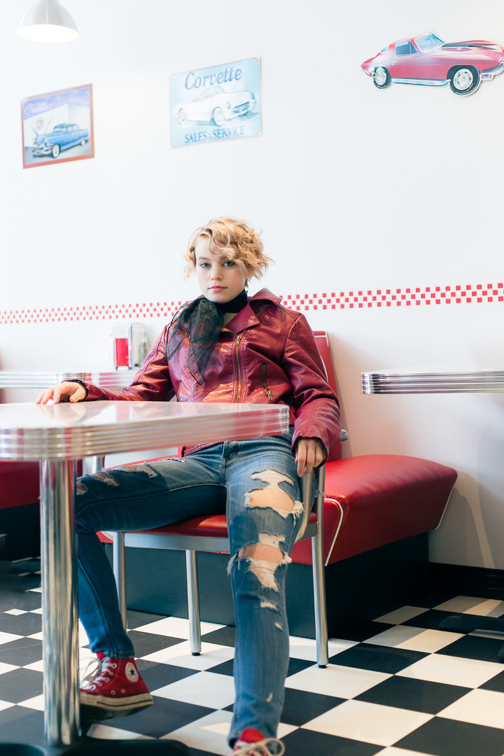 senior session at a diner with red jacket