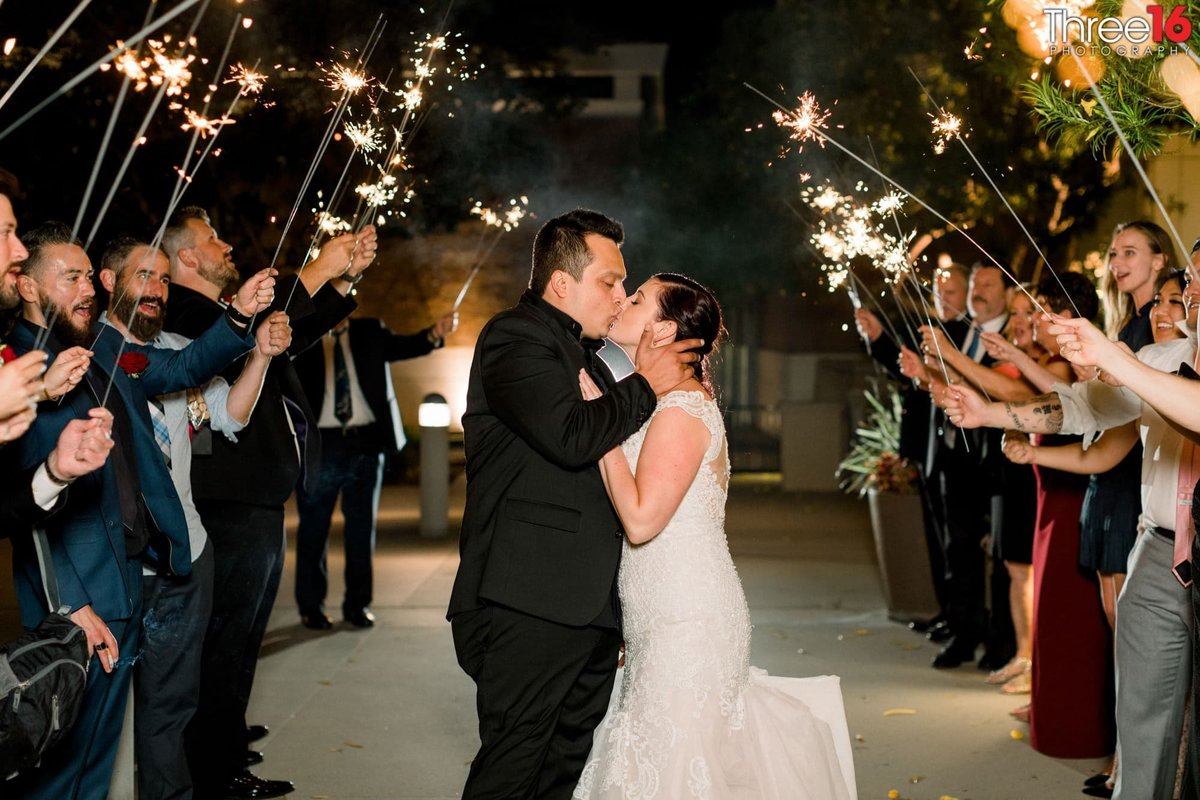 Bride and Groom stop for a kiss while walking under the human tunnel of sparklers