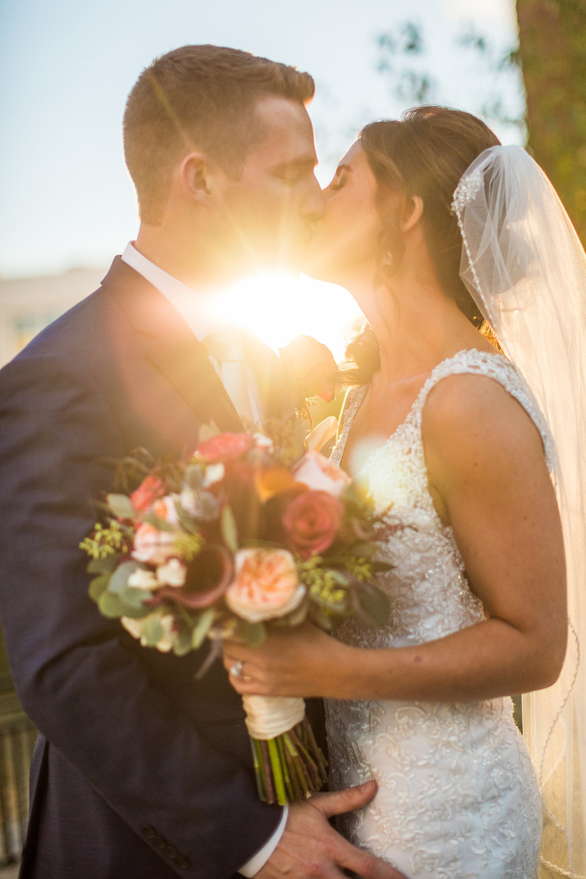 bride and groom kissing with sunset between them