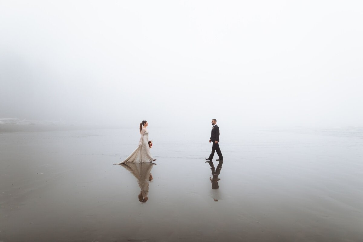 Bride and Groom walk towards each other on foggy  PNW beach