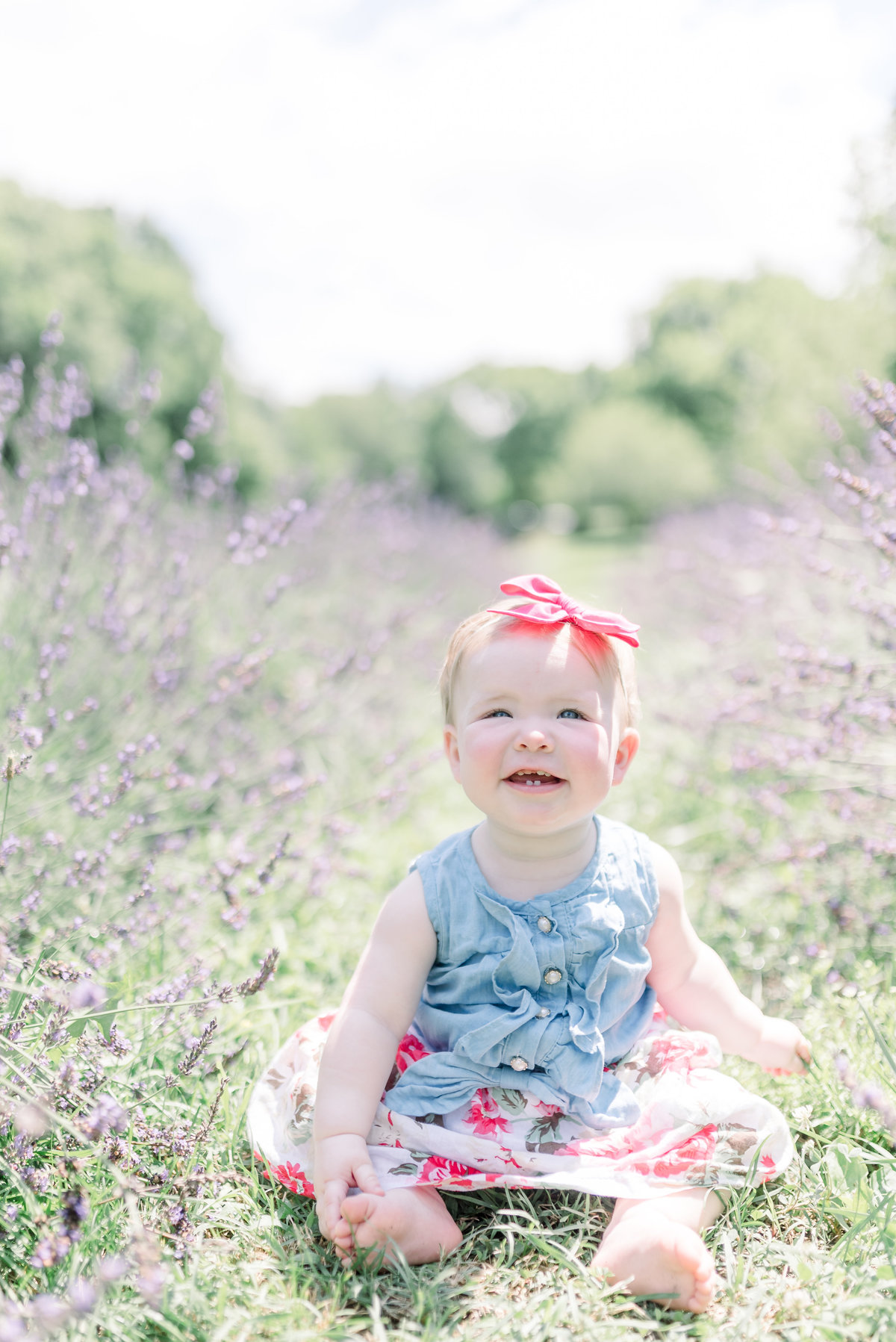 1 year old girl sitting in a lavender field and smiling up at camera