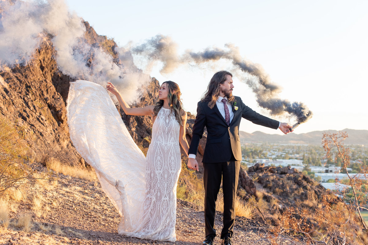 bride and groom hold hands and look opposite ways while groom holds black smoke bomb on mountain in phoenix arizona