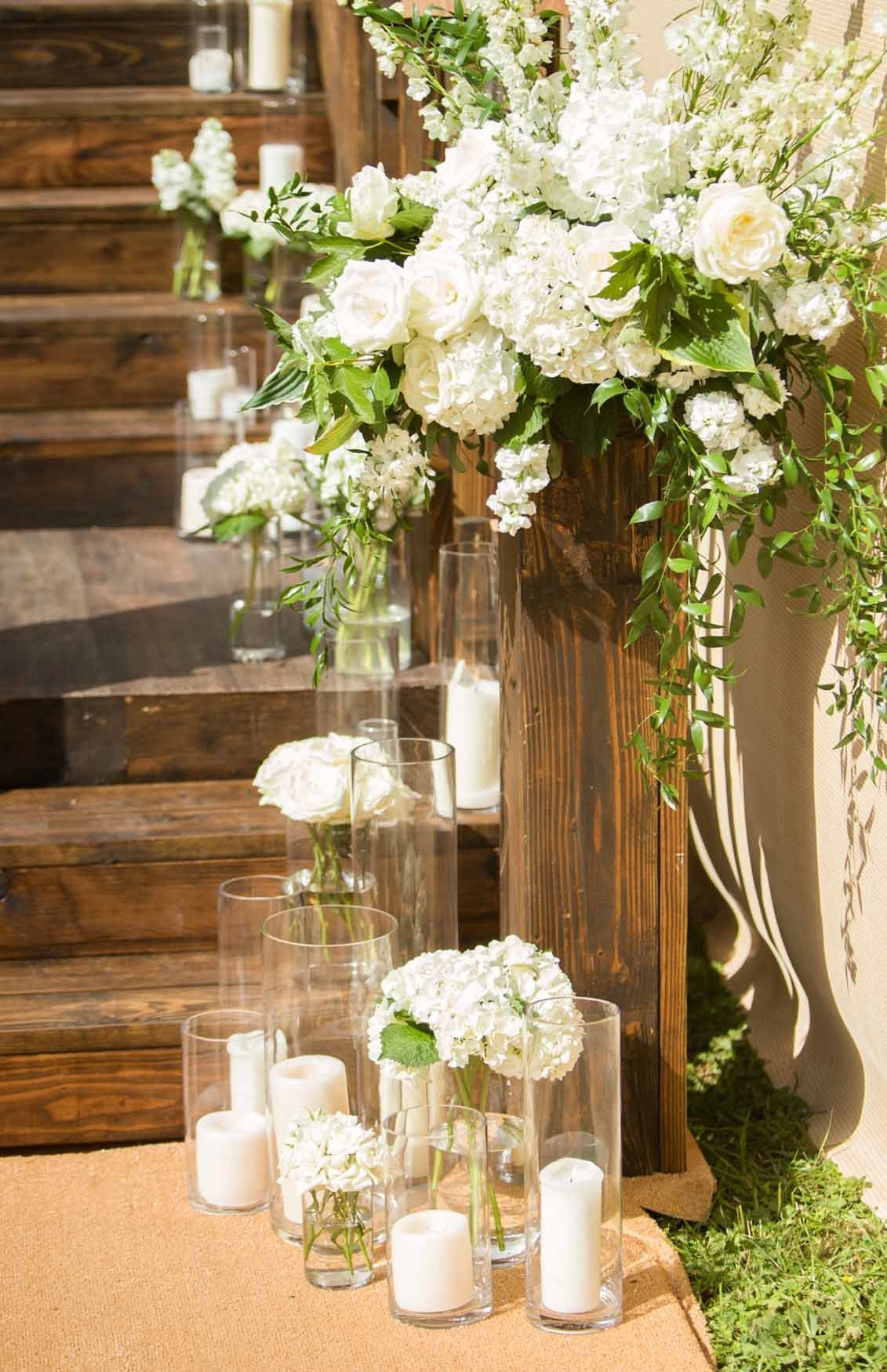 Large white flower arrangement and candles on a wooden staircase