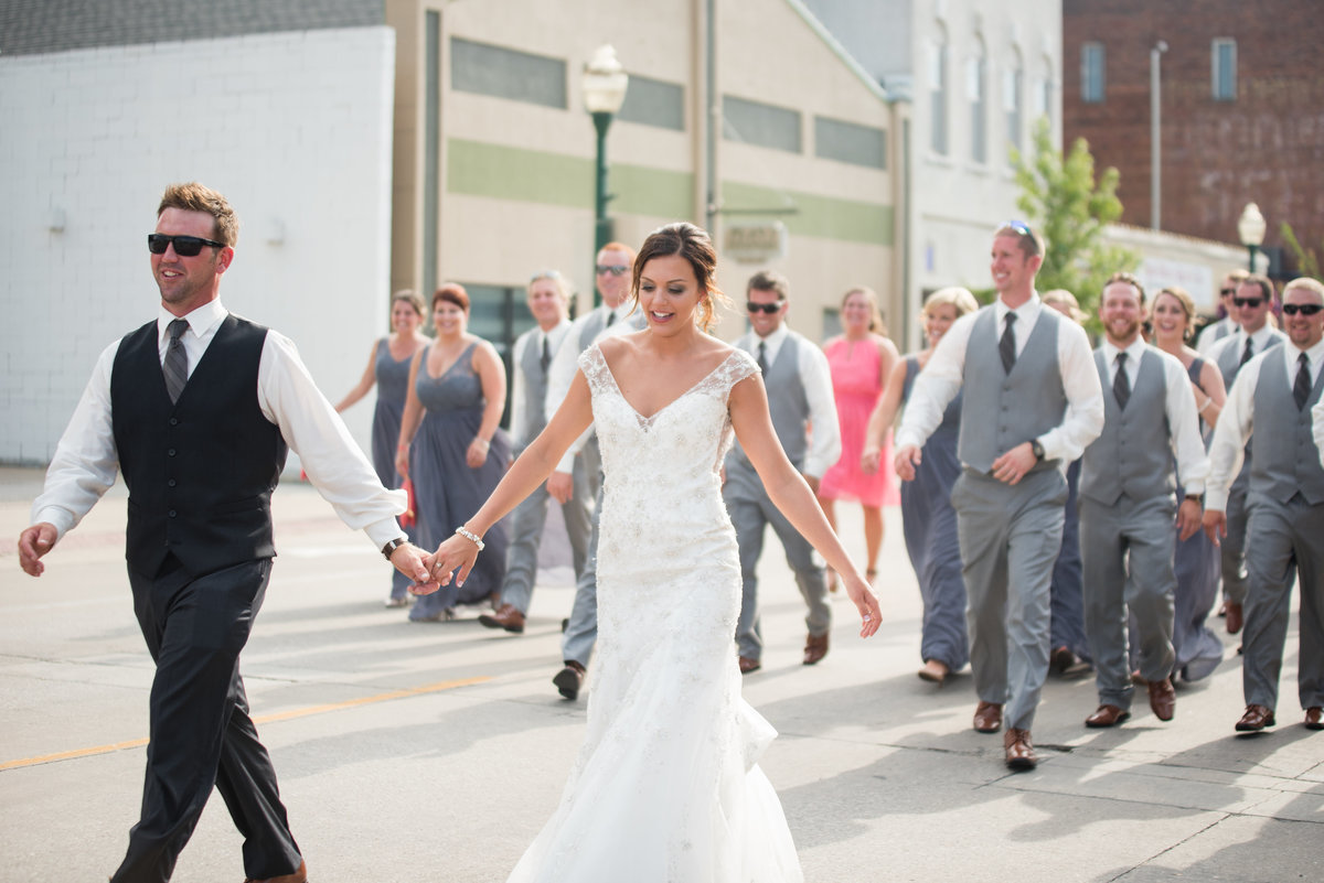 bride and groom leading wedding party walking on street smiling