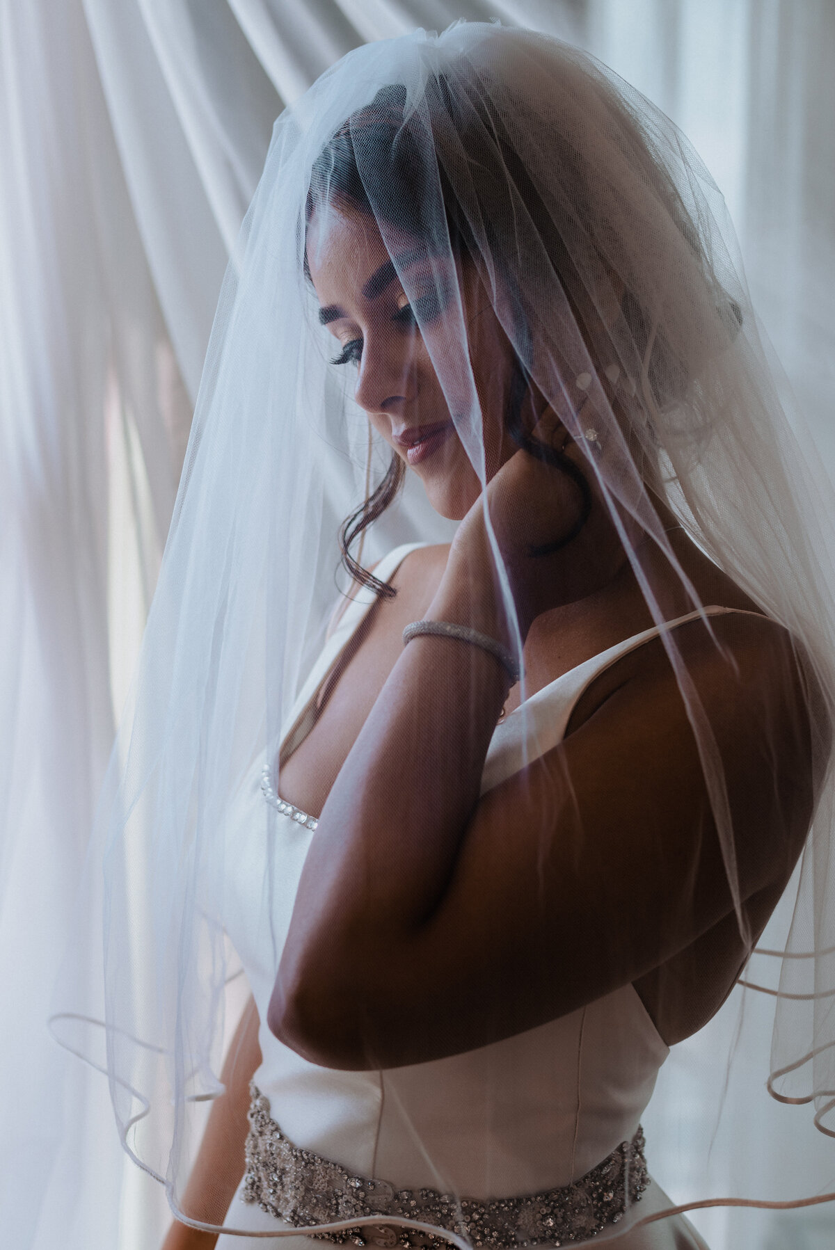 Bridal portrait by a window with veil
