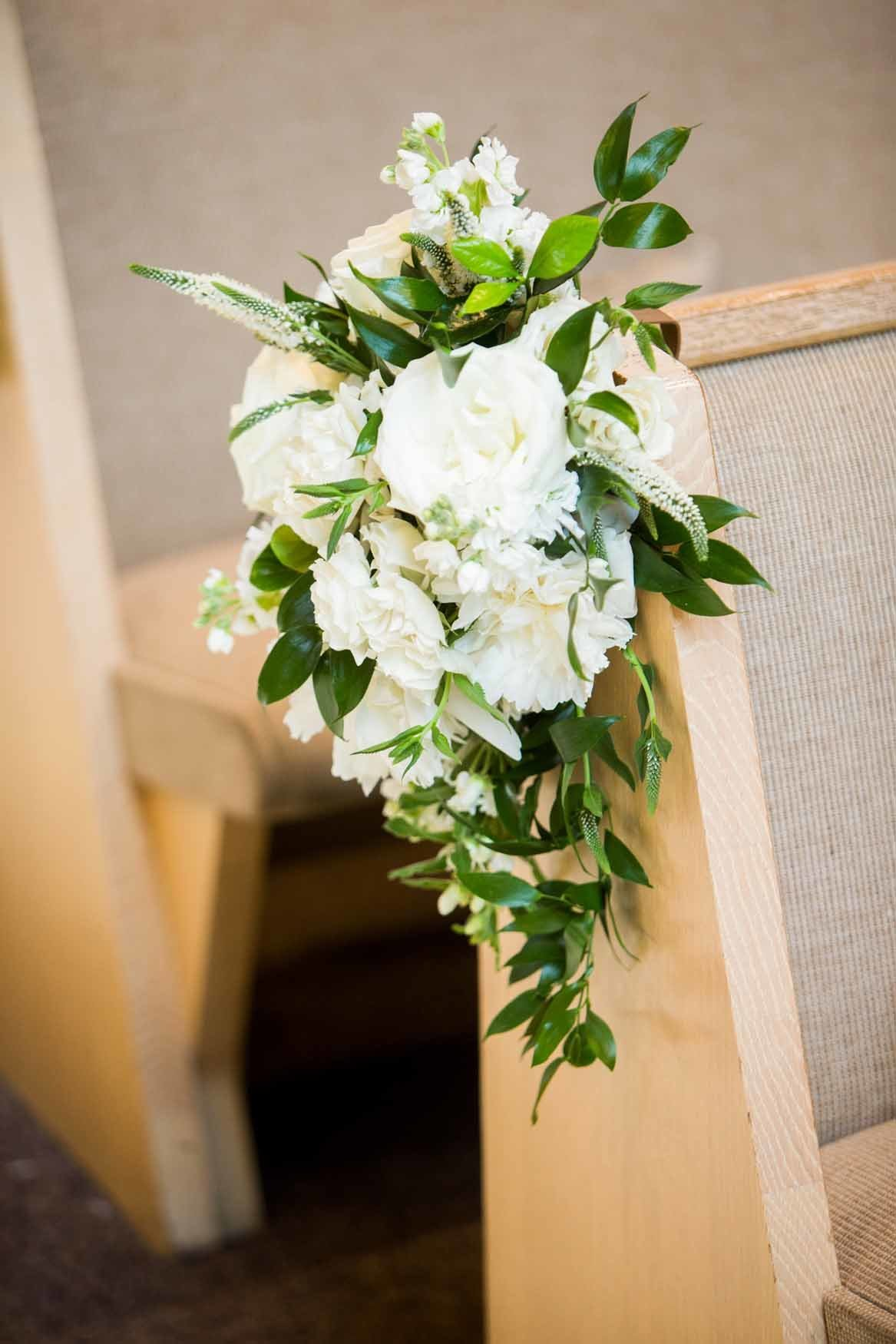 Wedding ceremony pew clips with roses and greenery