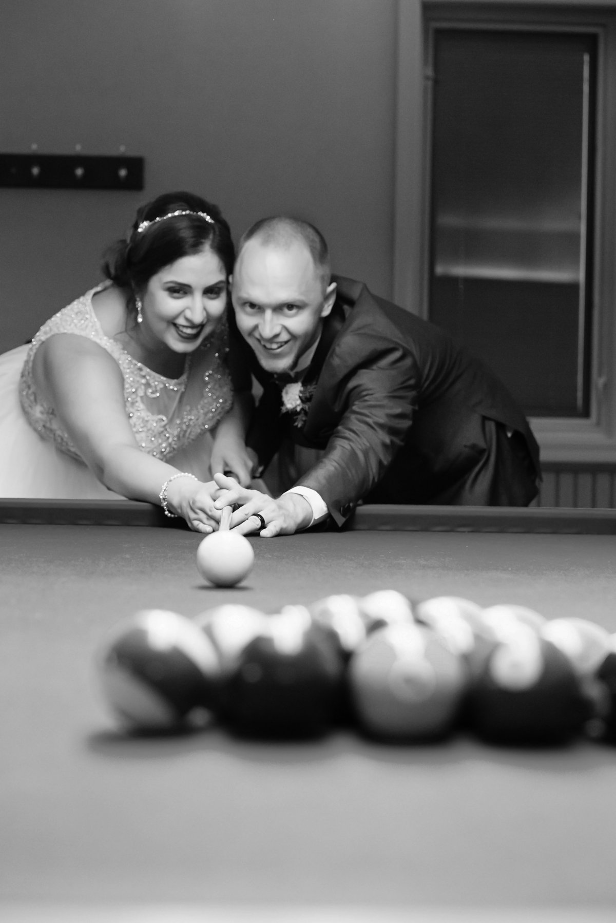 bride and groom playing pool