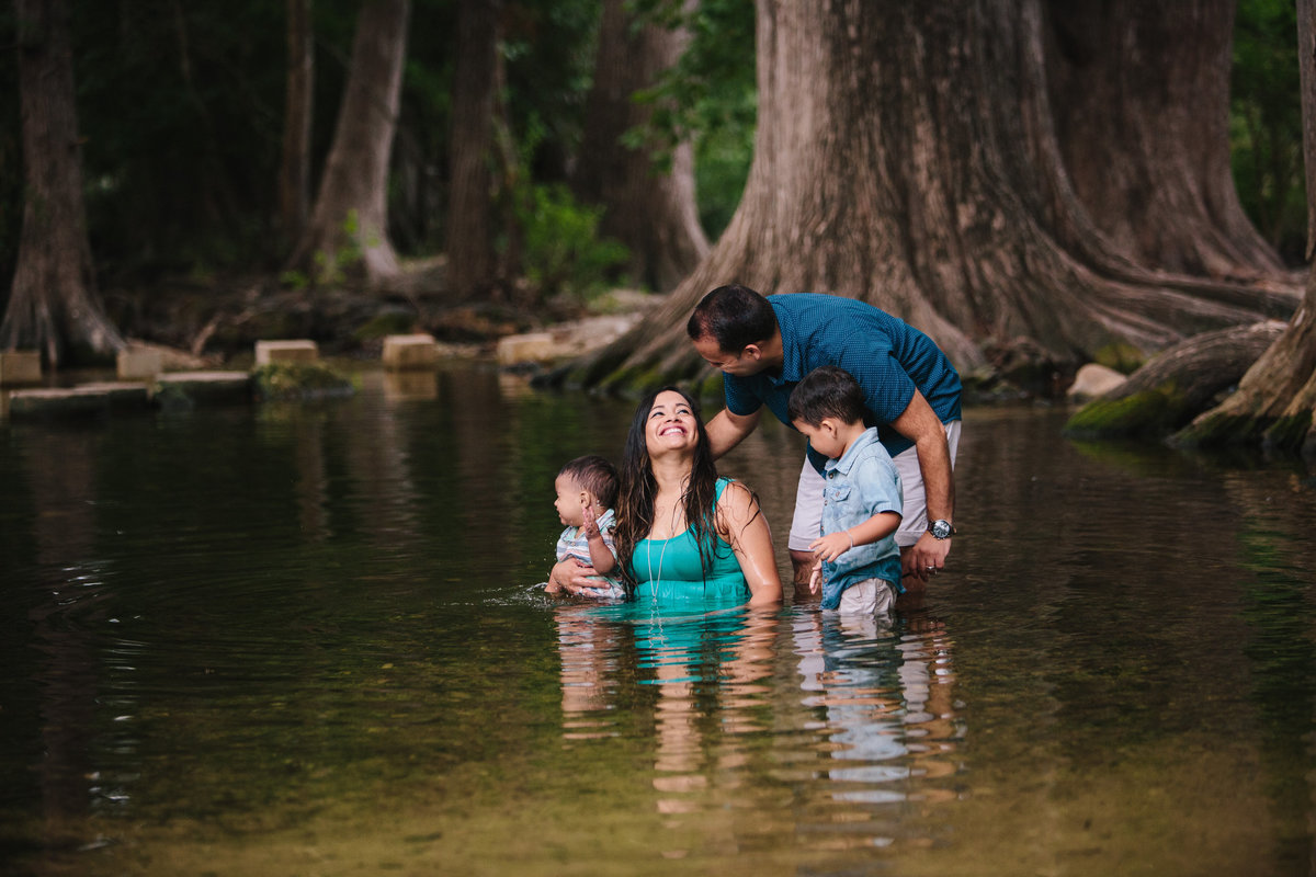 family portrait of couple sitting in river playin with their children by San Antonio photographer