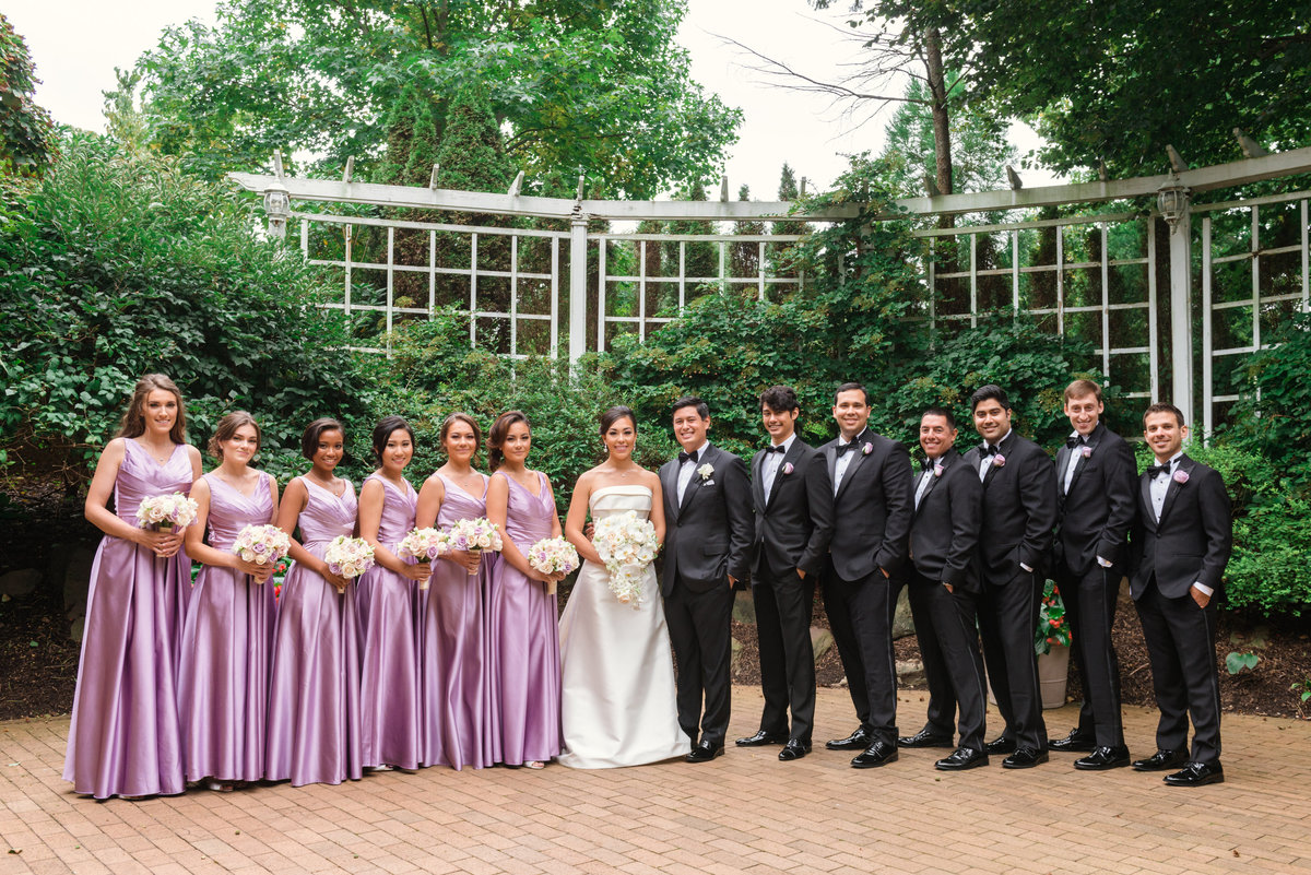 photo of bride and groom with entire bridal party in the outdoors garden at The Garden City Hotel