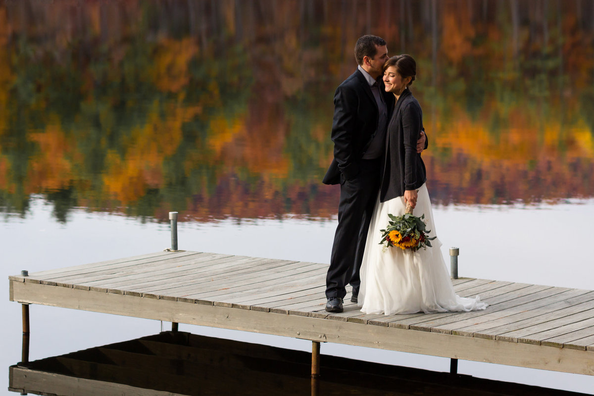 The bride and groom kiss on a dock in front of the fall trees reflected in Sebago Lake in Maine for their fall elopement