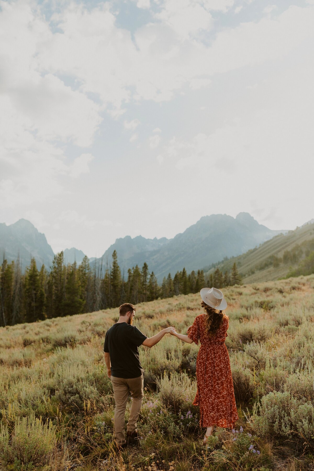 couple walking in a field in the mountains