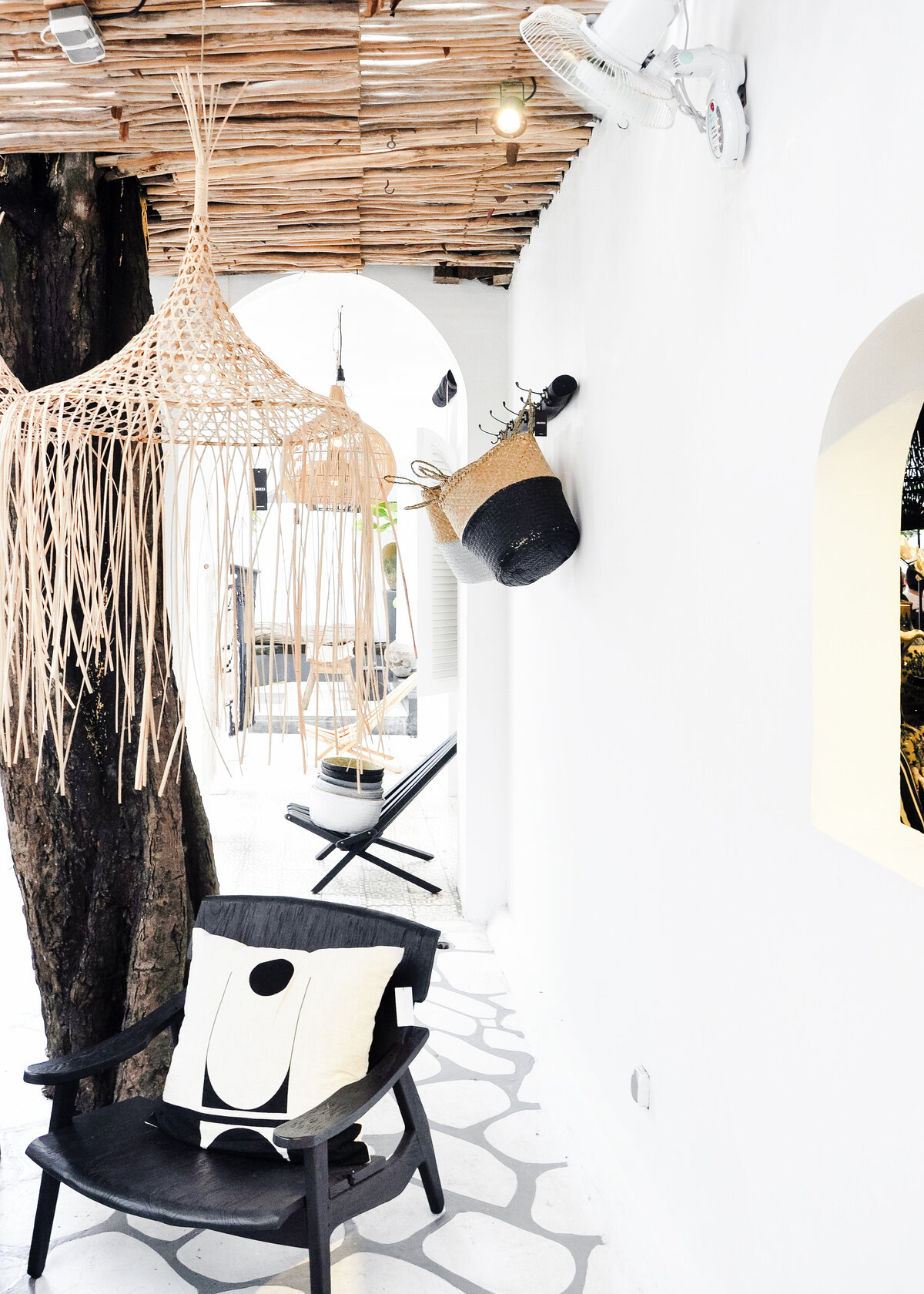 A white terrace in Spain is styled with a black deck chair, and wicker baskets with hanging raffia pendants.