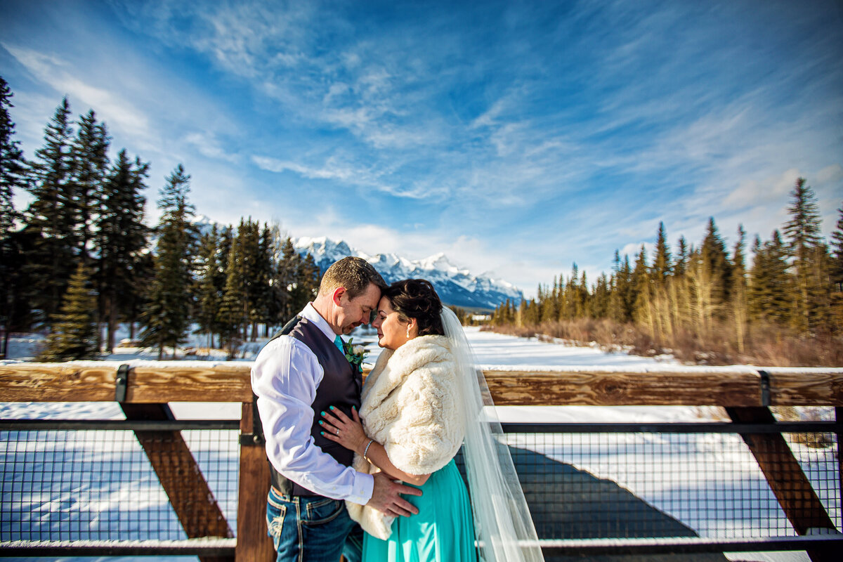 Winter elopement photo. Fur coat and veil with snowy background and blue skies.