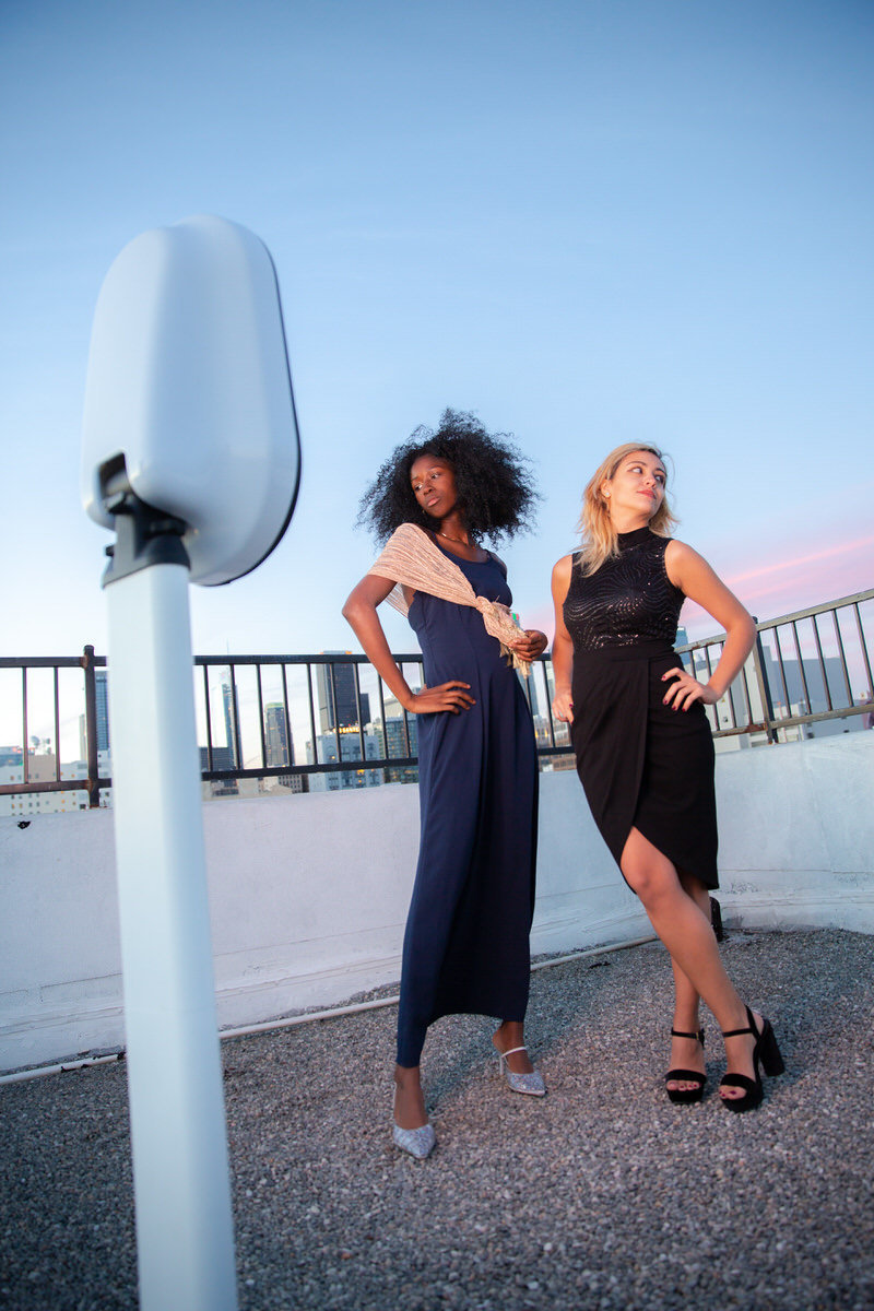 Two women using a photobooth on a city rooftop.