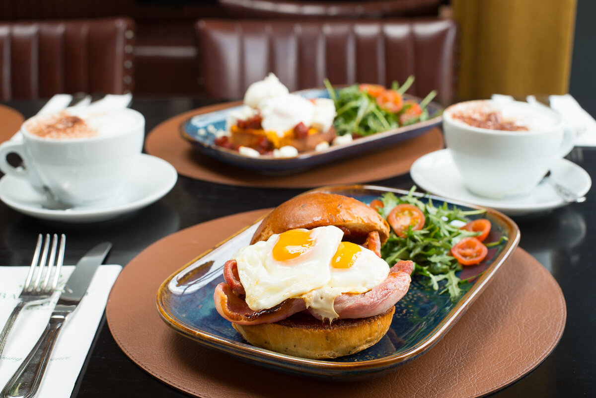 eggs and bacon in a bap with coffee