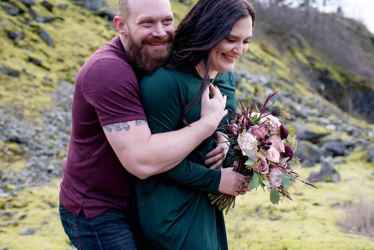 a woman holding a pretty bouquet by flowers by alana  laughs as her fiance gives her a big bear hug