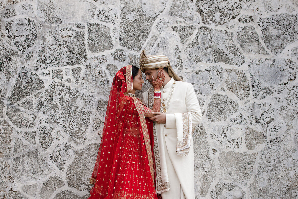 Indian bride and groom pose in front of wall at the Coral Gables Country Club