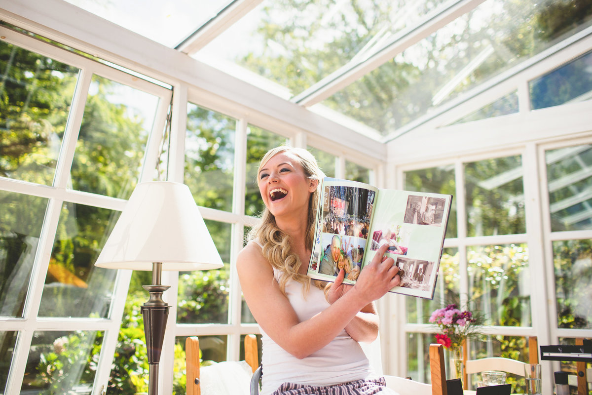 bride looking at hen party photo album and laughing in conservatory on morning of the wedding