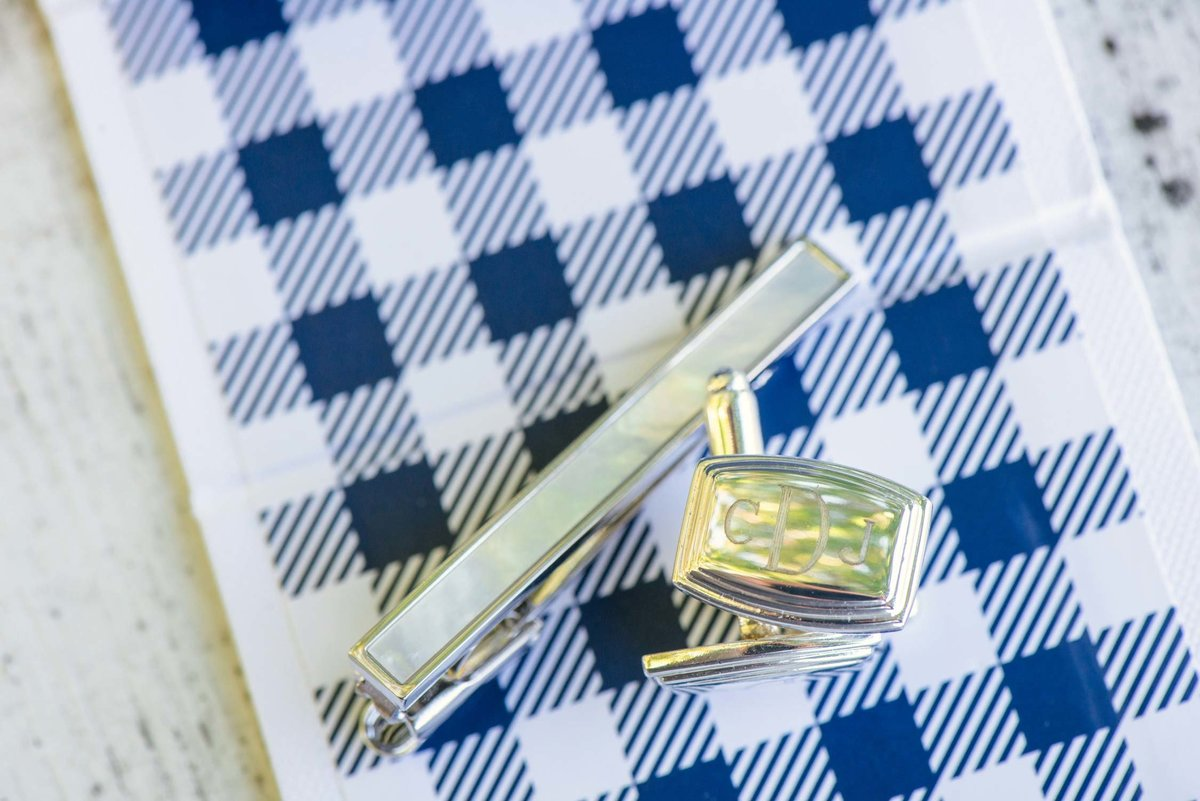 Groom's cufflinks and tie clip on blue plaid background at The Ram's Head Inn