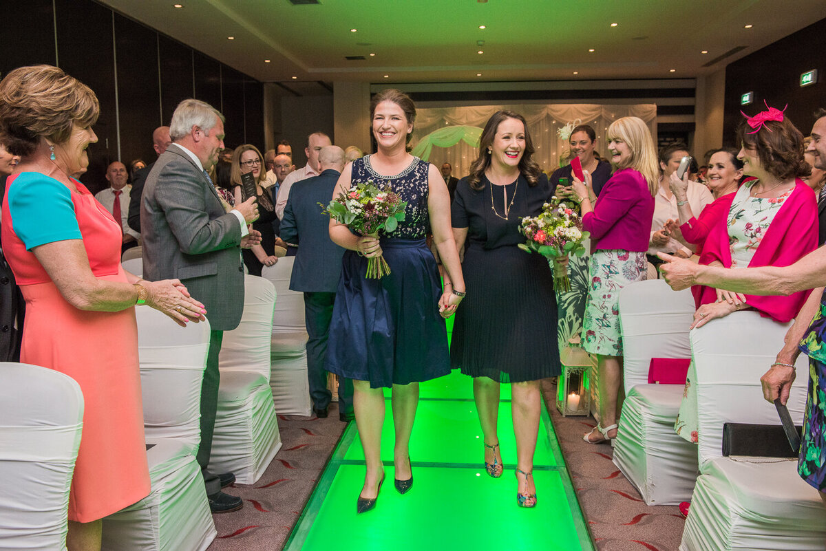 Two brides walking up a neon green aisle wearing navy dresses