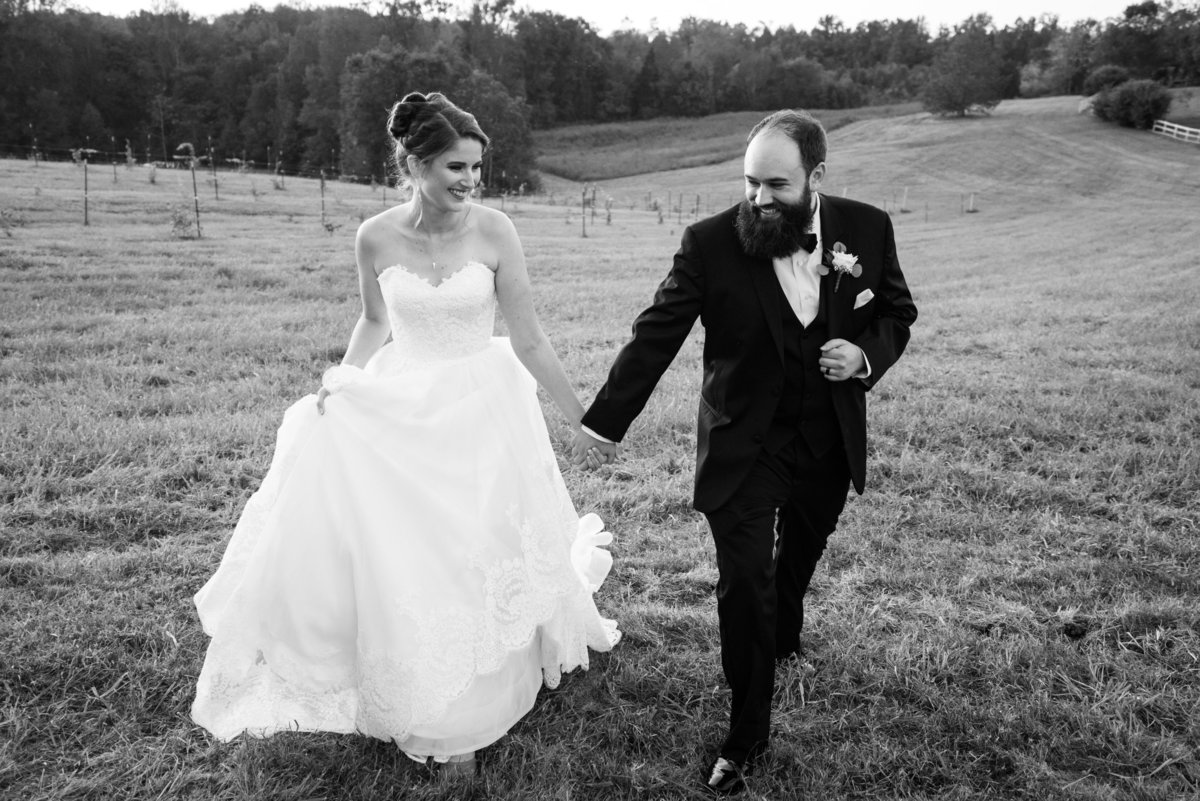 bride and groom walking up hill joyfully at estate at white hall wedding by va wedding photographer