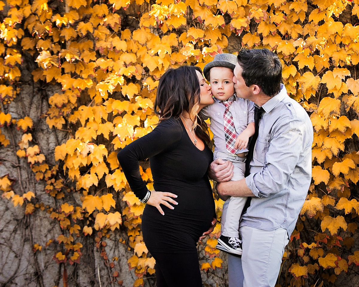 Mom and dad holding toddler boy and kissing his cheeks while mom is holding her pregnant belly in front of yellow autumn leaves.