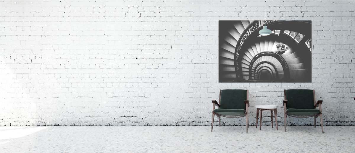 A large art canvas  mounted on a white brick wall.