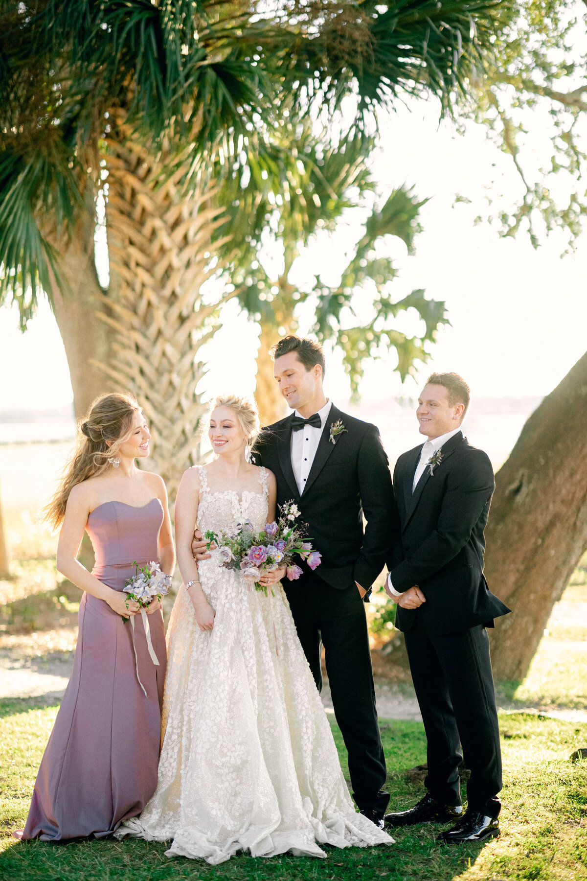 Bride and groom with maid of honor and best man by trees outside wedding