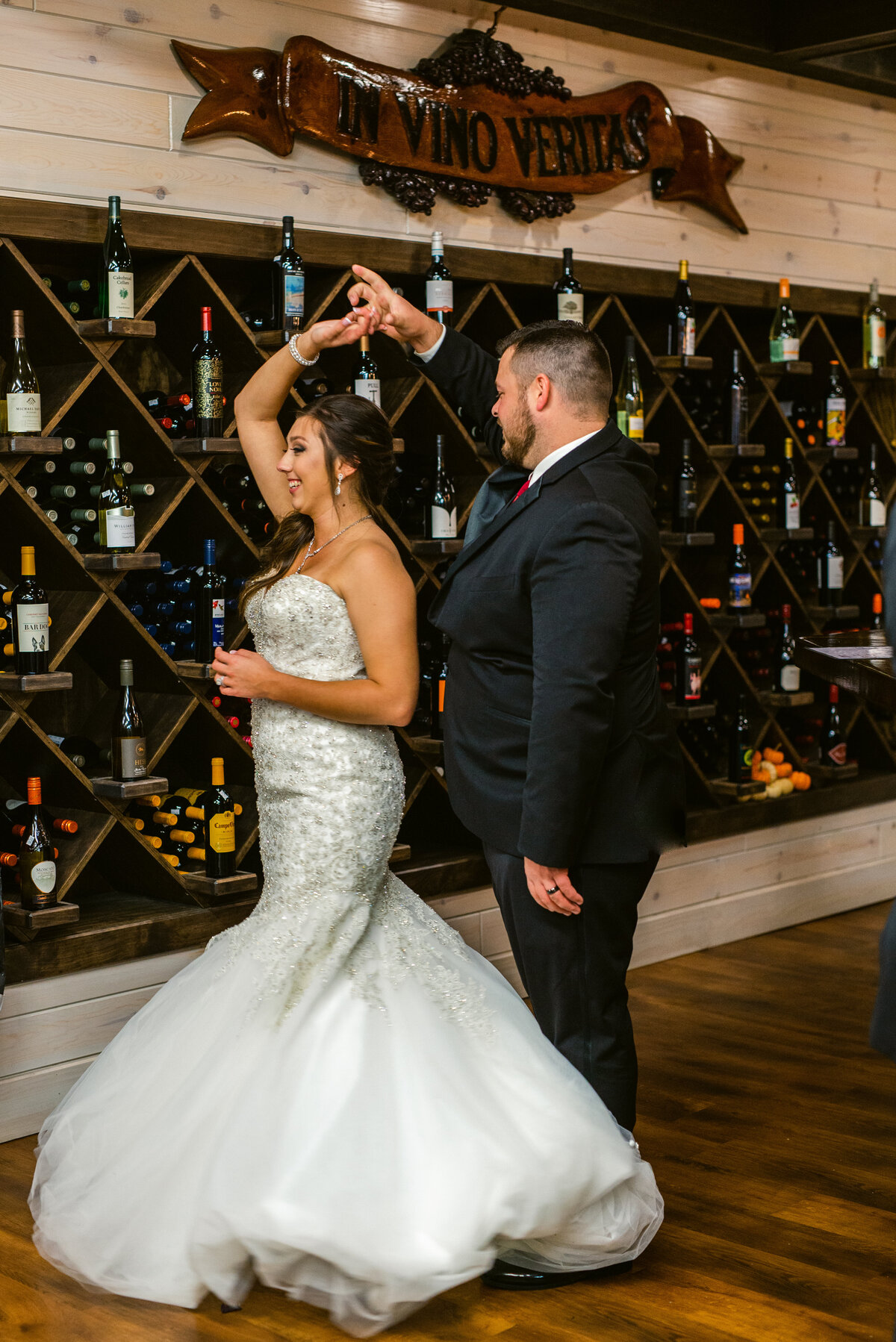 Bride and Groom dancing in the aisle of a wine store.