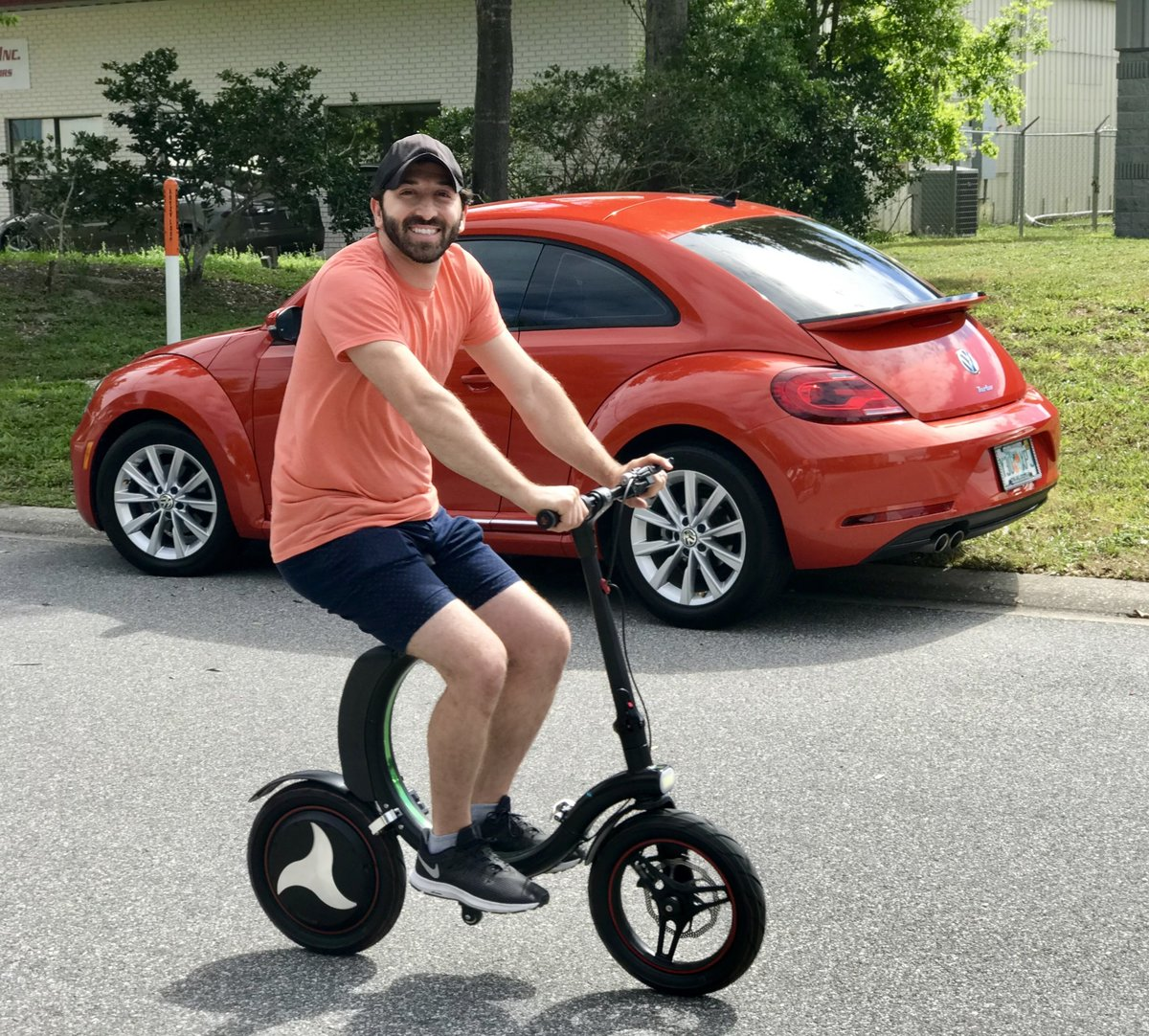 Guy riding his Go-Bike Q1 after parking his Red Volkswagon