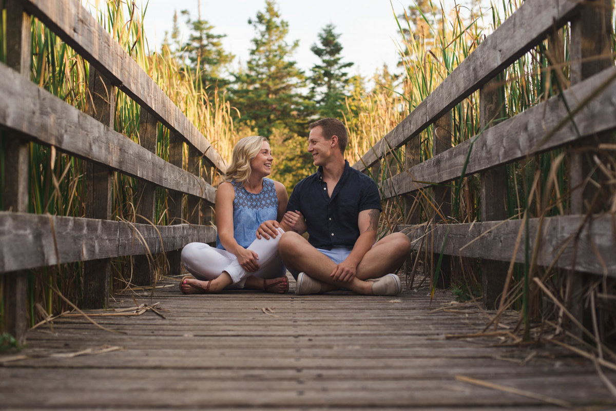 couple sitting cross-legged on wooden bridge next to one another laughing