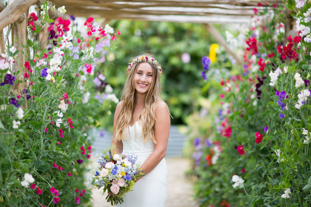 Bride with sweetpea arch at River Cottage Wedding Devon