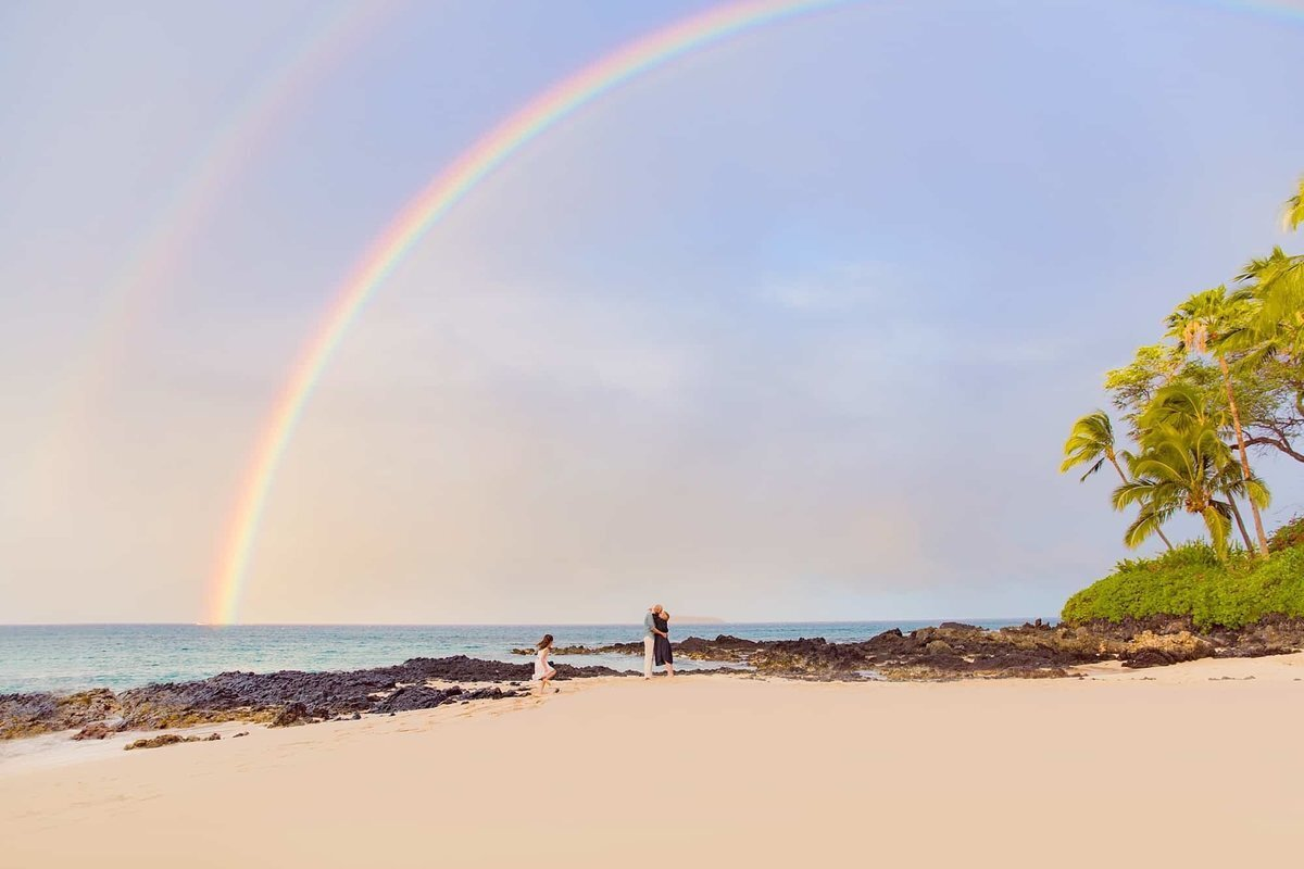 Girl running to parents under a rainbow at Secret Beach in Maui