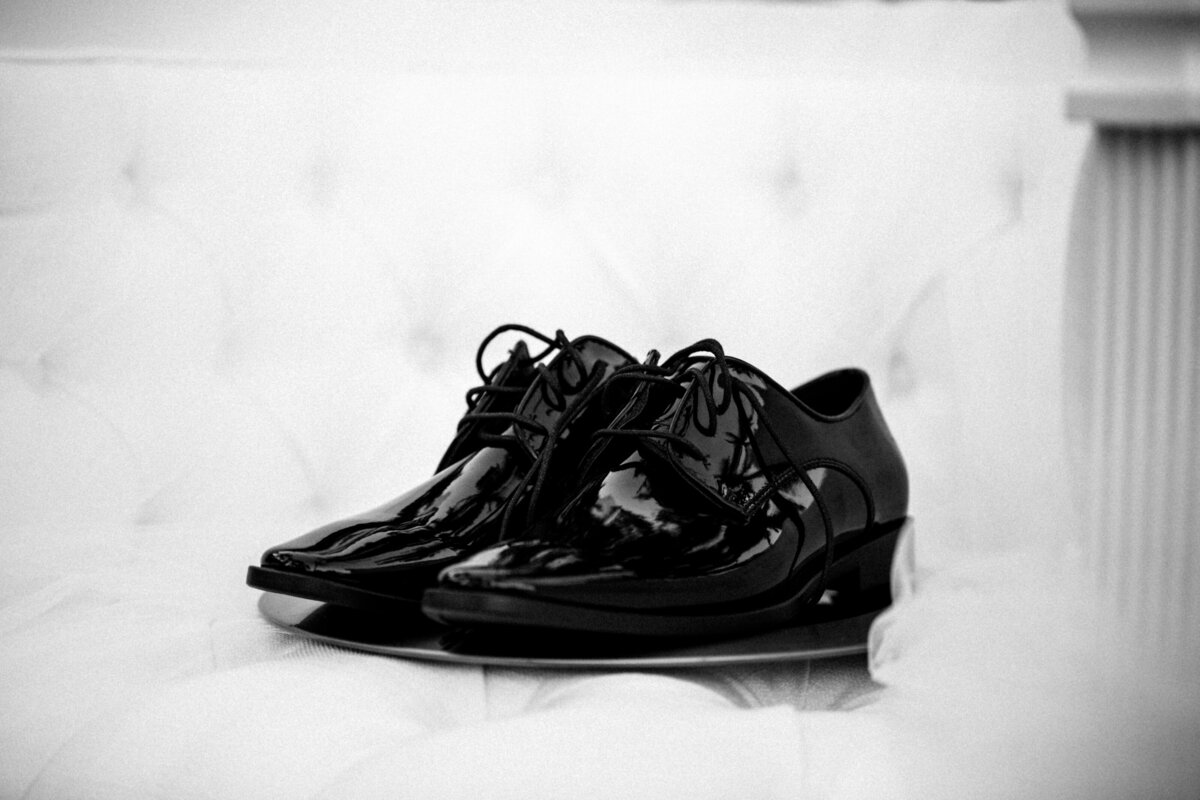 detail shot of groom's black shiny patent leather lace up shoes
