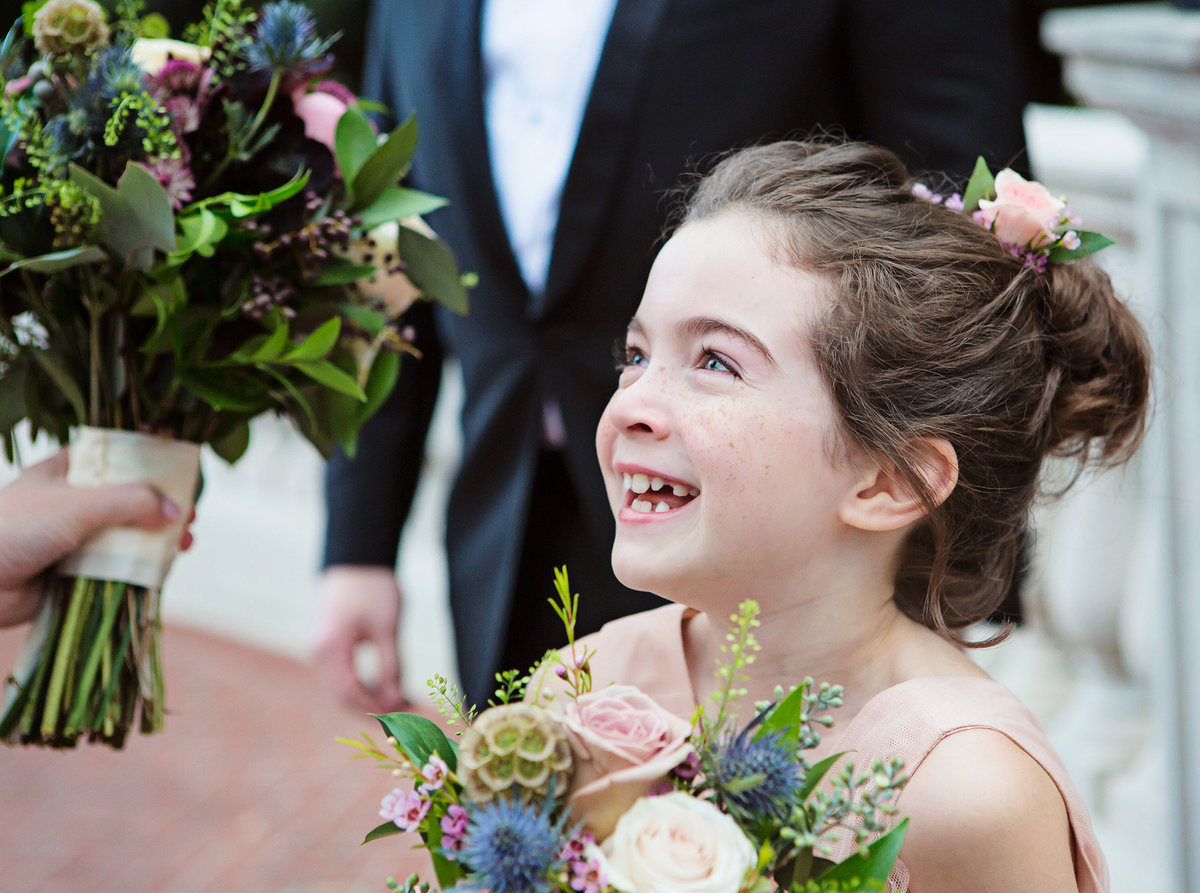 NOLA flower girl looks up excitingly at bride