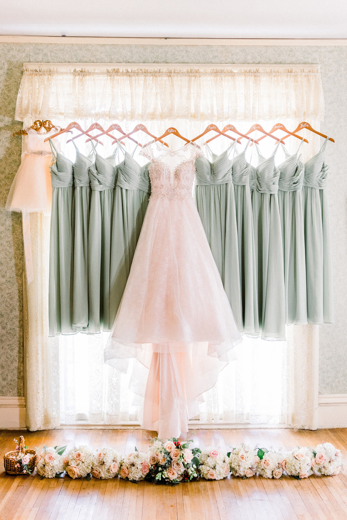 beauitufl vintage wedding dresses hang in the window of cedar falls woman's club