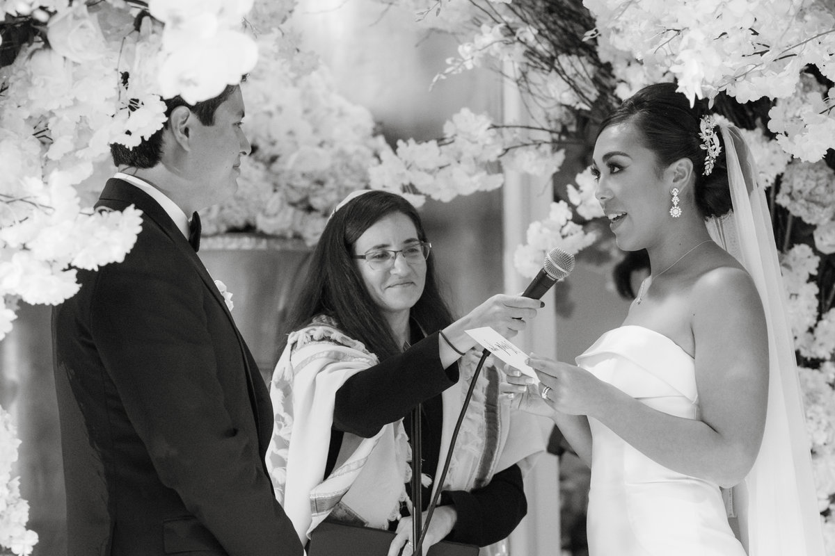 black and white photo of bride and groom during ceremony at The Garden City Hotel