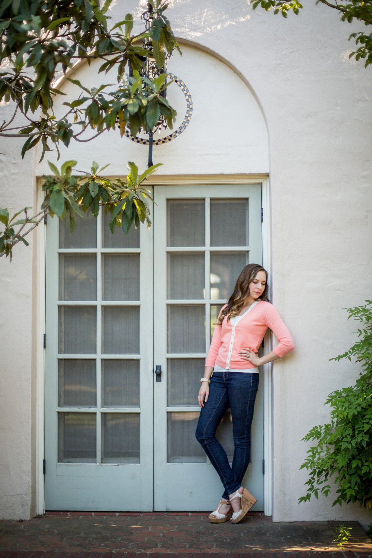 high school senior girl hand hip standing by door taken by San Antonio senior photographer
