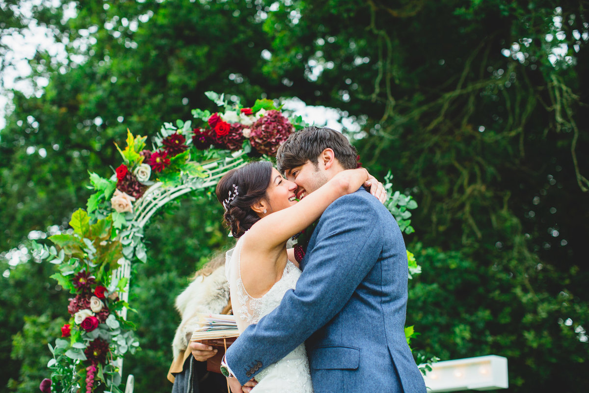 outdoor wedding ceremony under a flower arch - first kiss