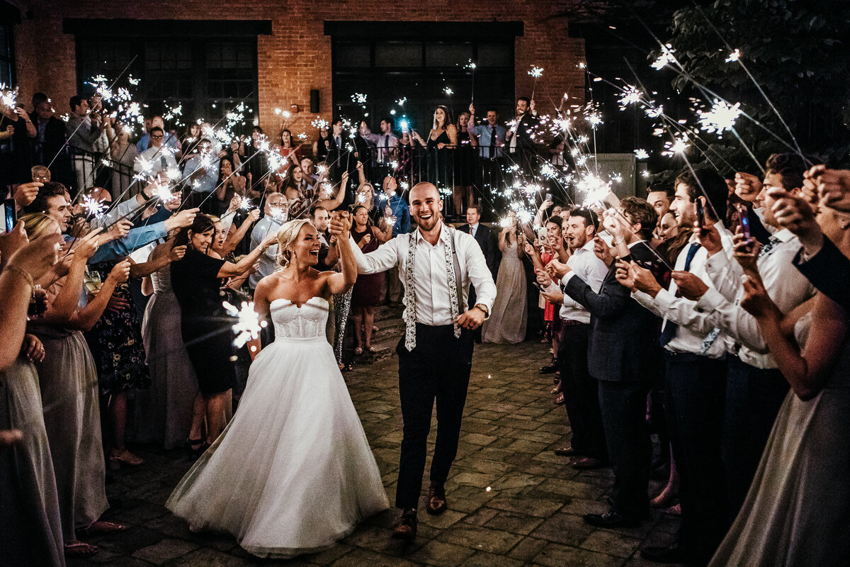 Bride and groom walking out of wedding ceremony with guests holding sparklers in Buffalo, New York